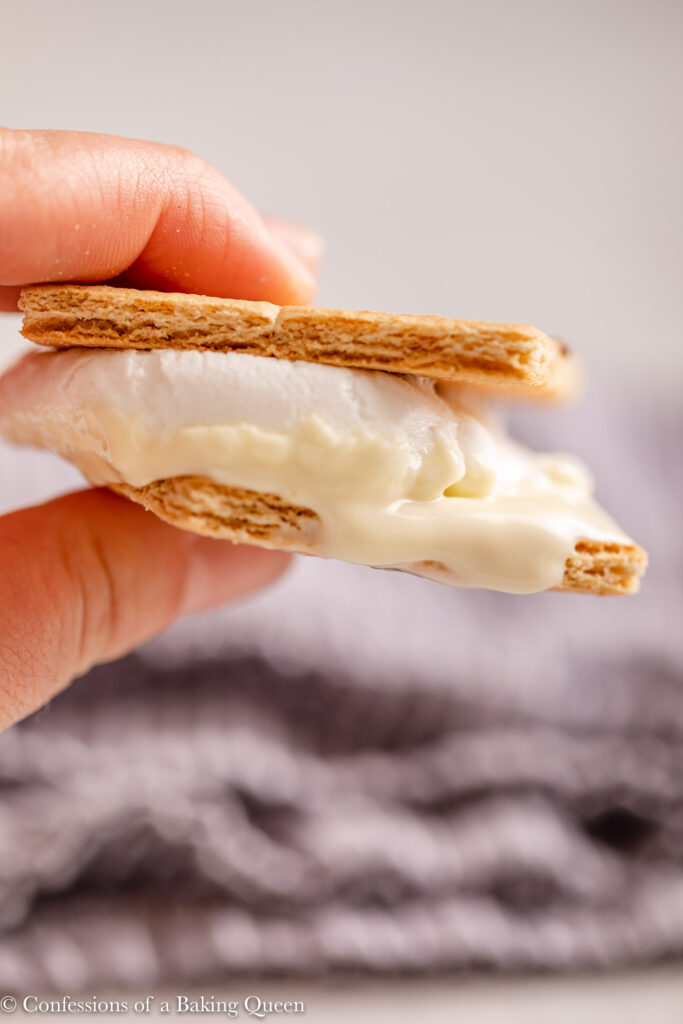 hand holding a white chocolate smores over a blue linen
