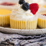 mini cheesecakes with whipped cream and berries on a speckled plate on a light grey surface with a blue linen