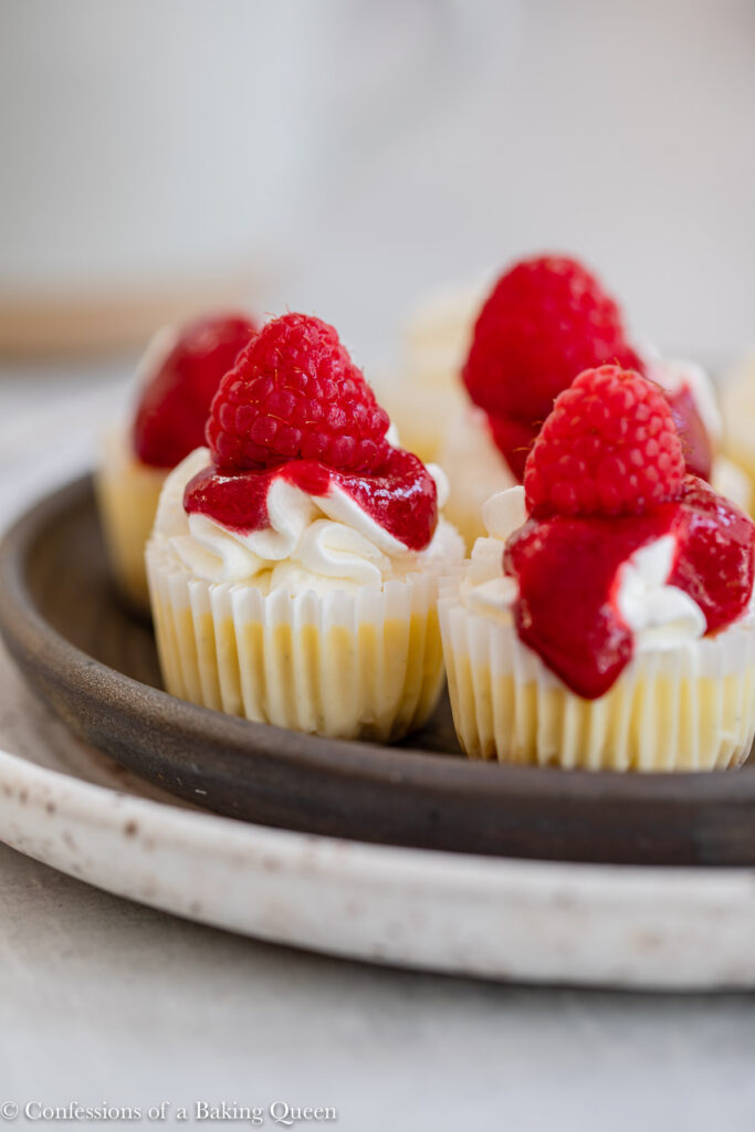 mini raspberry cheesecakes on a black plate on a light grey surface