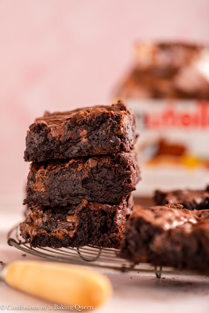 stack of nutella brownies on a wire rack with a nutella jar in the background on a light pink surface with a knife
