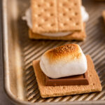 toasted marshmallow on top of chocolate and a graham cracker on a metal baking pan on a light grey surface