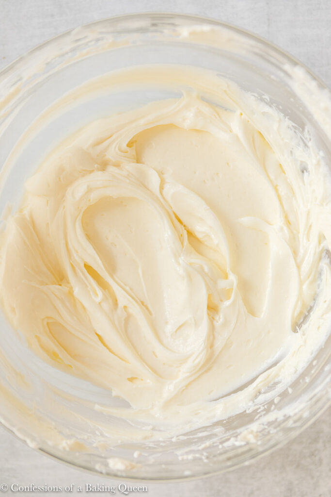 up close of cream cheese once the sugar has been mixed in on a light grey surface