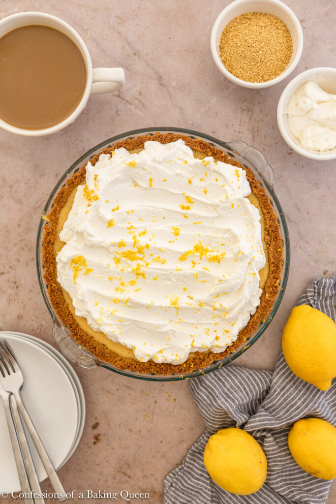 creamy lemon pie served with plates an silverware and a cup of coffee and lemons on a light brown surface