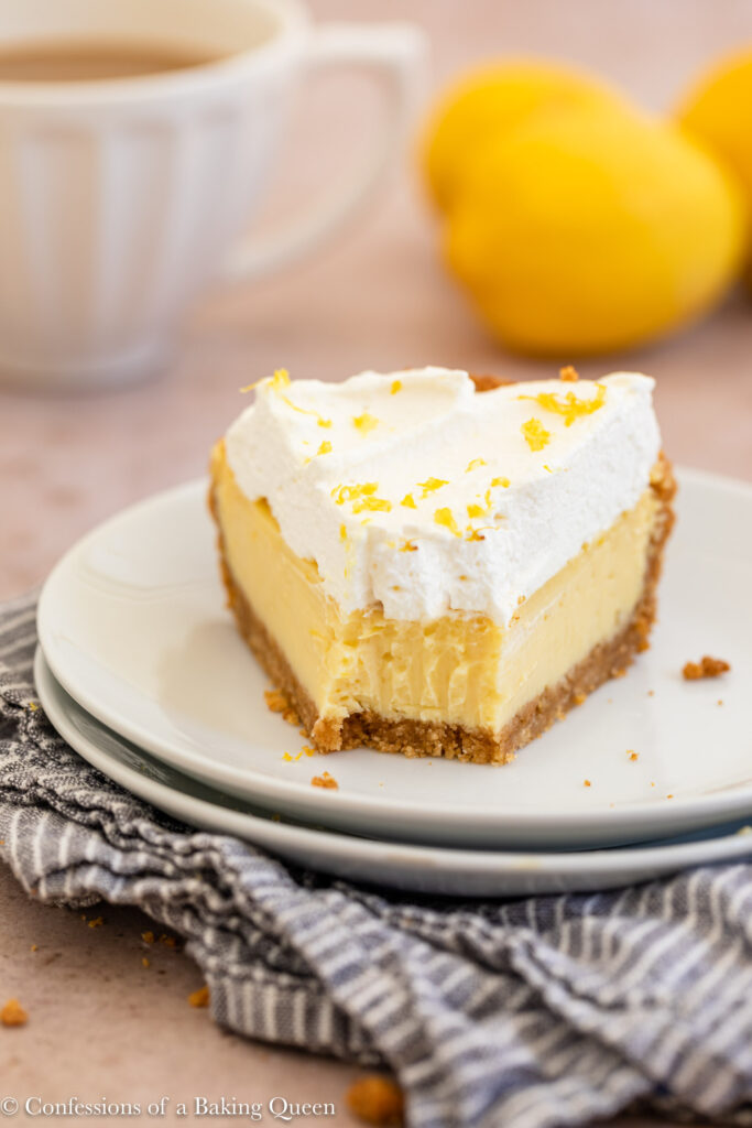 slice of half eaten creamy lemon pie on a stack of white plates on top of a blue linen on a light brown surface with a cup of tea and lemons in the background