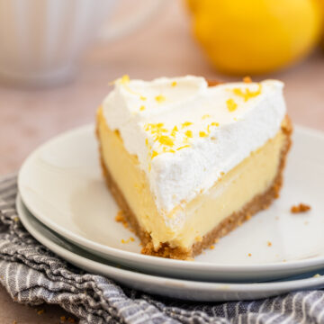 slice of lemon cream pie with whipped cream on top on a white plate on a blue linen on a light brown surface with a cup of coffee and lemons in the background