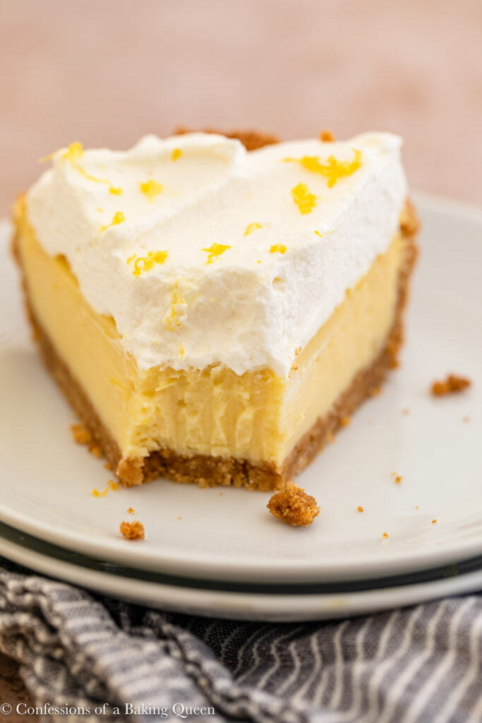 up close of creamy lemon pie with a bite missing on a couple white plates on top of a blue and white linen on an light brown surface