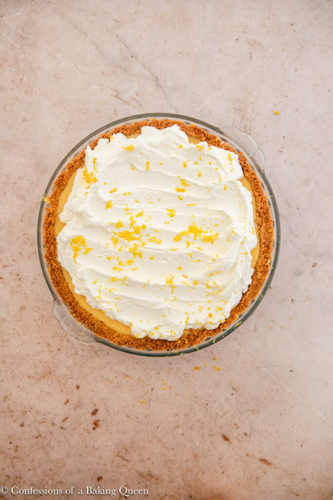 whipped cream spread on top of lemon pie topped with lemon zest on a light brown surface