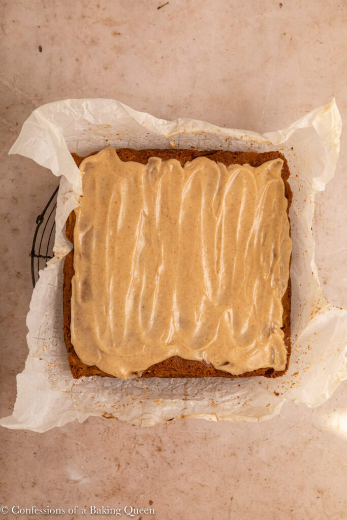 brown butter frosting spread on top of square peach cake on top of parchment on a wire rack