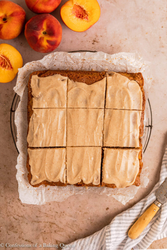 brown butter peach cake cut into slices on a wire rack on a light brown surface with a white and blue linen and a knife and next to some peaches