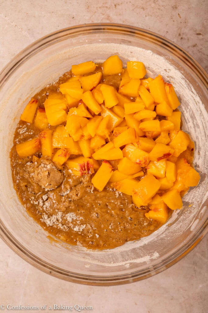 close up of peach chunks added to cake batter in a glass bowl on a light brown surface