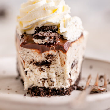close up of a half eaten slice of no bake oreo cheesecake on a white plate with a fork on a white marble surface