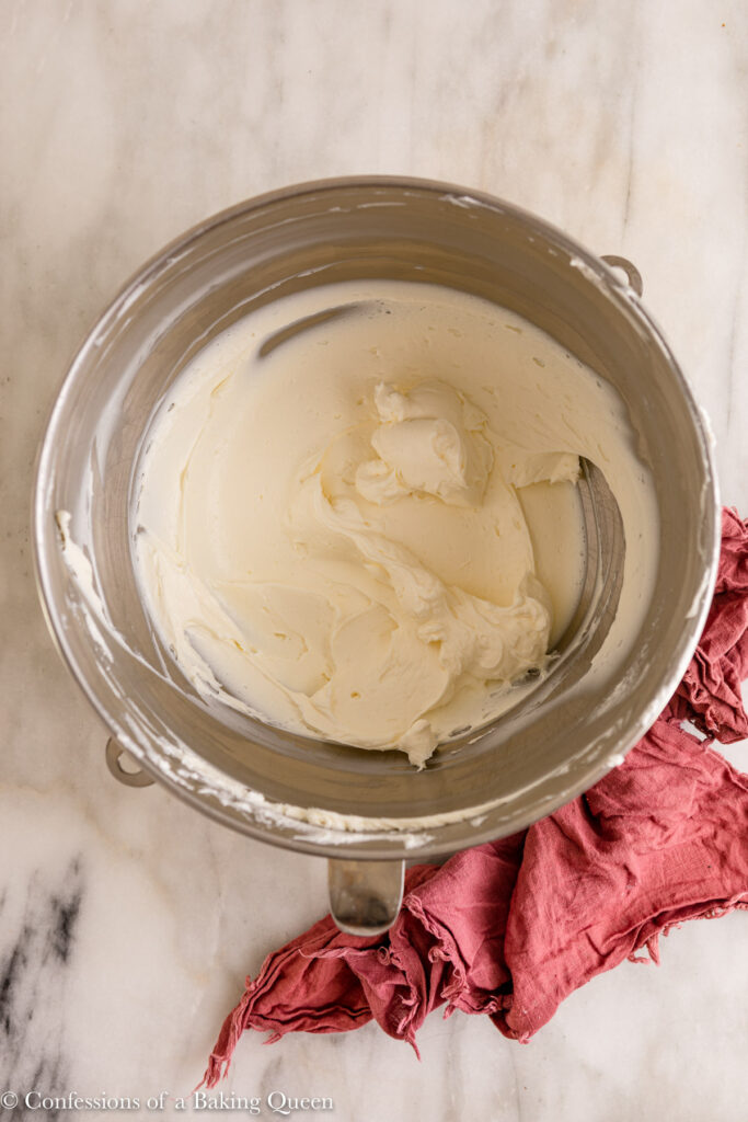 cream cheese whipped until light and fluffy in a metal mixing bowl on a marble surface with a pink linen