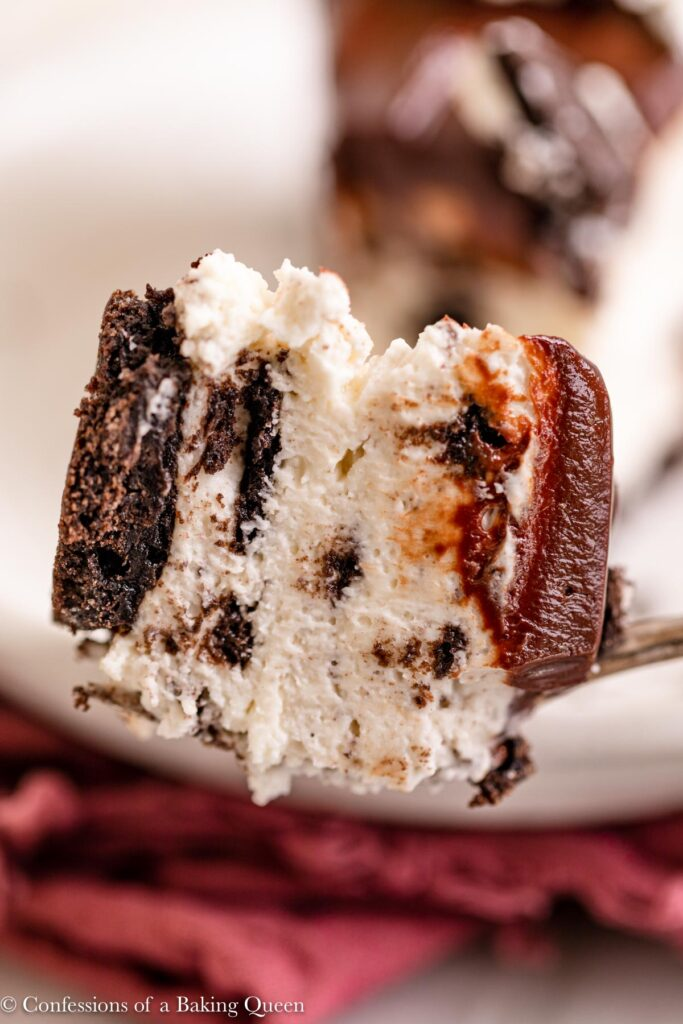 fork holding a bite of no bake oreo cheesecake over a plate with a pink linen on a marble surface