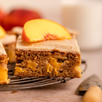 slice of peach on top of a peach cake on a wire rack next to a knife on a light brown surface