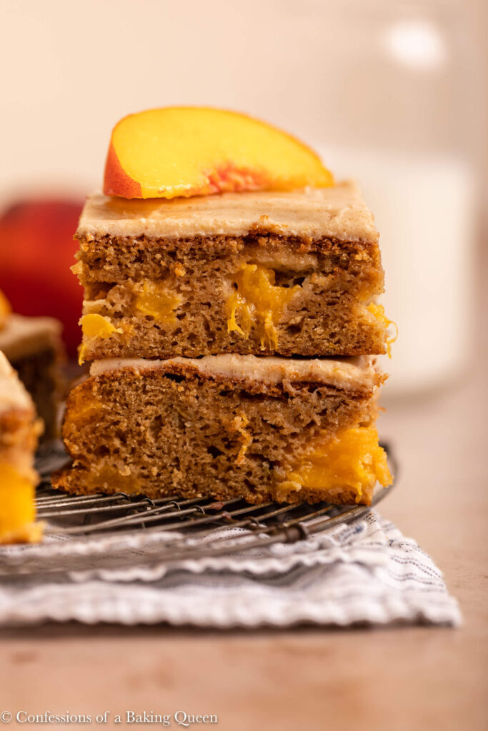 two slices of peach cake stacked on top of each other on a wire rack on top of a white and blue linen on a light brown surface
