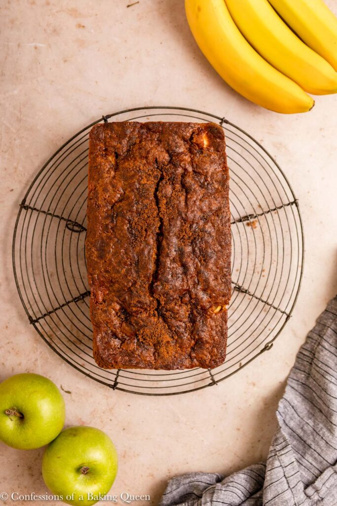 banana apple bread cooling on a wire rack on a light brown surface with a blue linen with some green apples and bananas