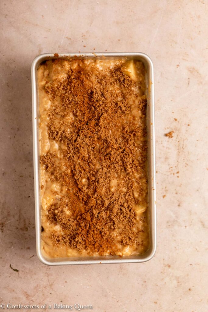 brown sugar and ground cinnamon added on top of banana apple bread batter on a light brown surface