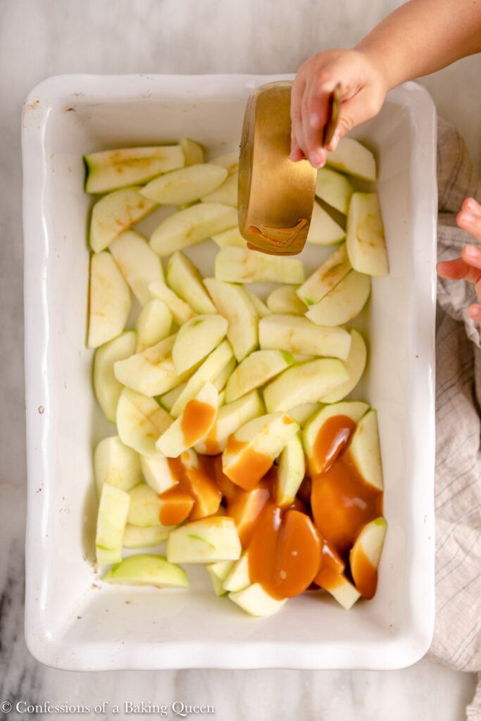 caramel poured on top of apples in a white ceramic baking dish on a marble surface with a grey and blue linen