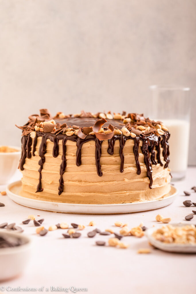 chocolate and peanut butter cake served on a white plate with a glass of milk on a light cream surface with peanuts and chocolate chips