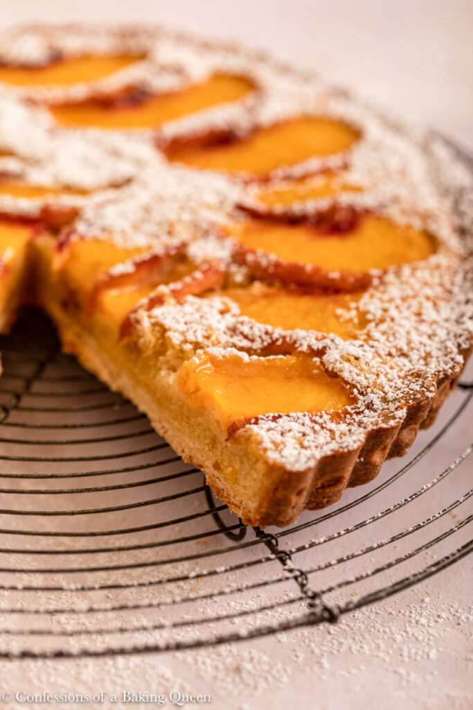 close up of cut open peach frangipane tart on a wire rack on a light surface
