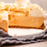 close up of cut open pumpkin cheesecake on a white platter on top of a blue linen on a light brown surface