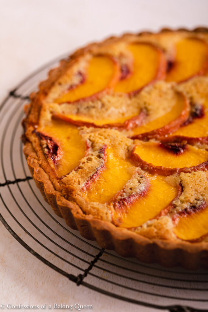 close up of peach almond tart cooling on a wire rack on a light surface