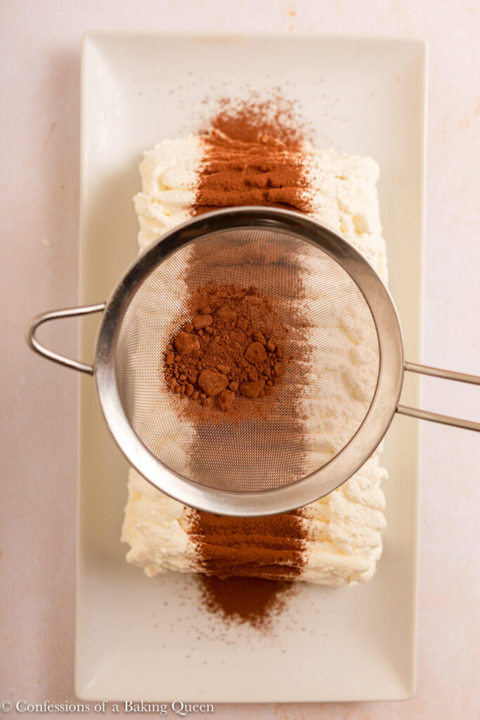 cocoa powder sifted on top of whipped cream on the ice cream cake on a light cream surface