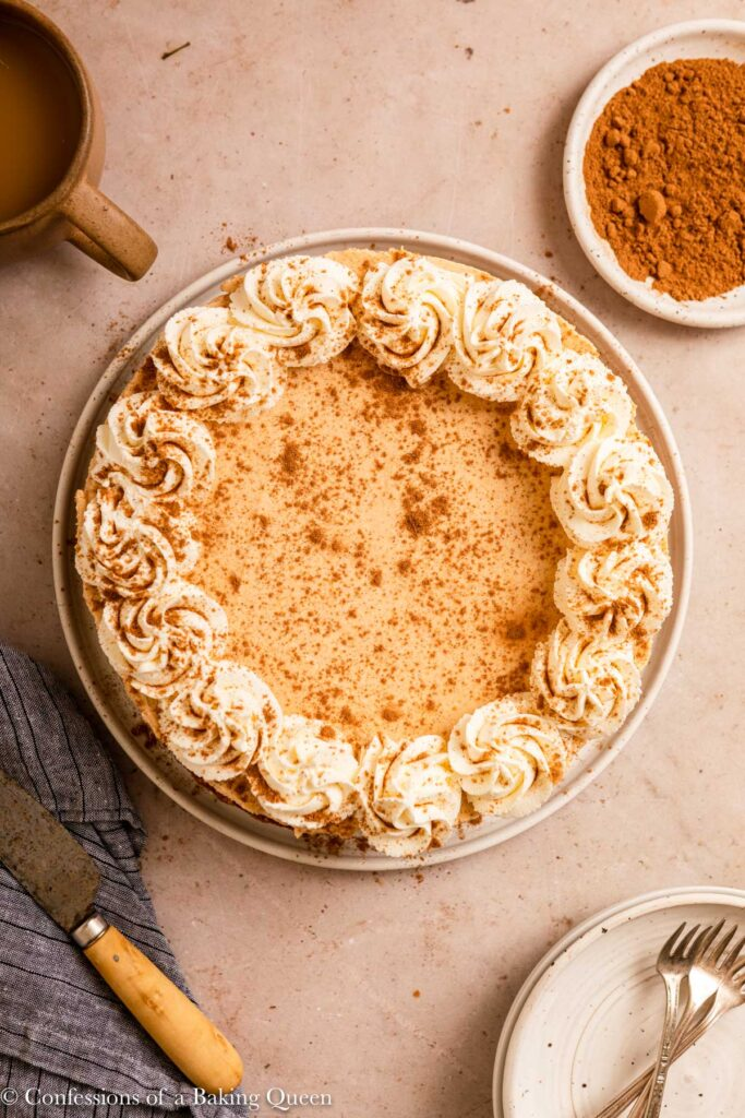 egg free pumpkin cheesecake next to a cup of coffee, knife, plate of spices, and serving plate s and forks on a light brown surface with a blue linen