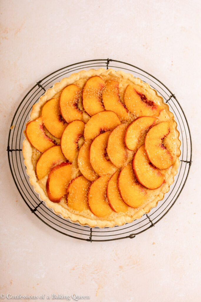 peach frangipane tart before baking on a wire rack on a light surface