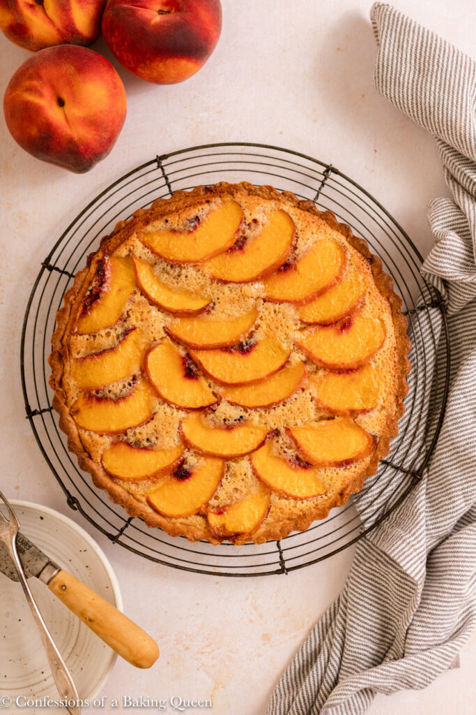 peach frangipane tart cooling on a wire rack on a light surface with a white and blue linen, three peaches, plate with knife and fork