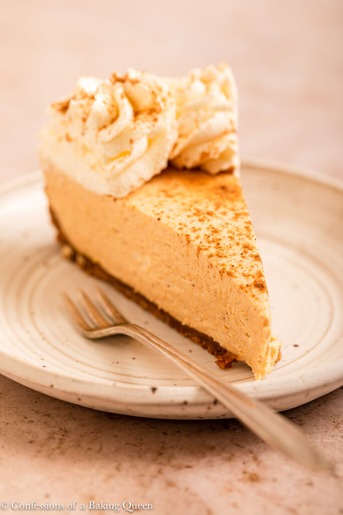 slice of no bake cheesecake on a white plate with a fork on a light brown surface with a blue linen