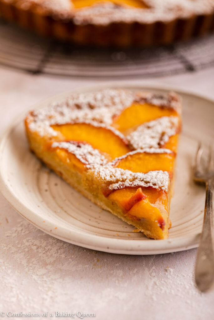 slice of powdered sugar covered almond peach tart with a fork on a white plate on a light surface with the whole tart in the background