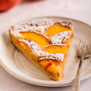 slice of powdered sugar covered peach frangipane tart on a white plate next to peaches on a light surface