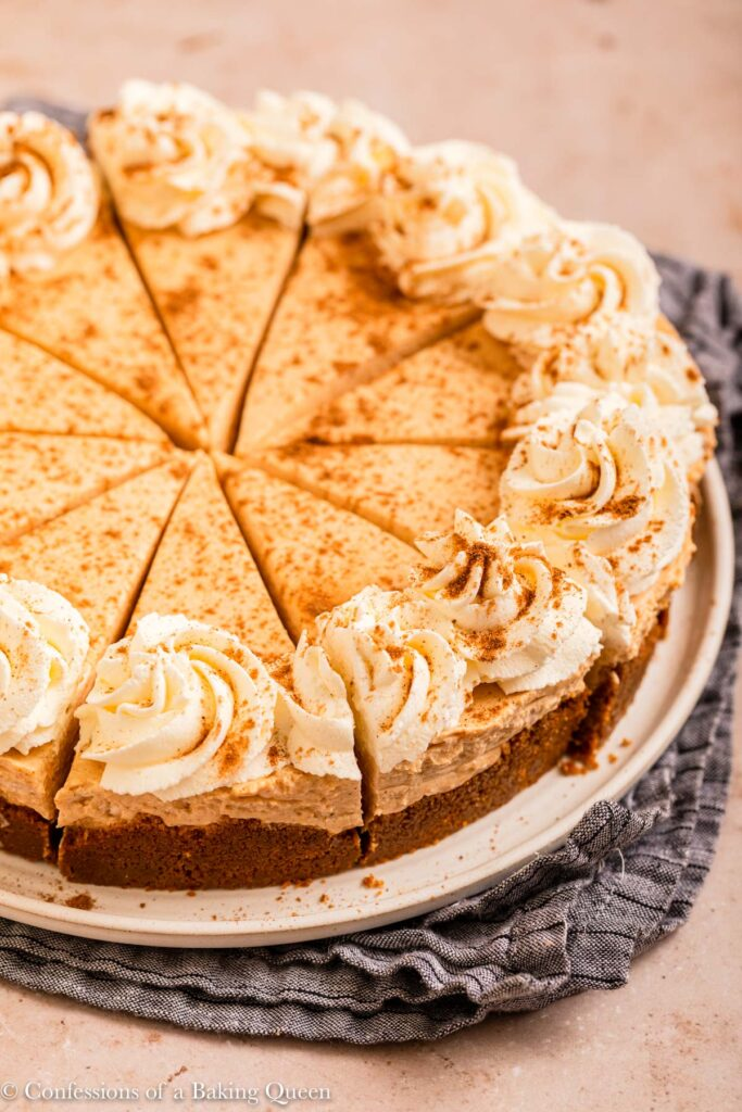 sliced egg free pumpkin cheesecake on a white serving platter on a light brown surface with a blue linen