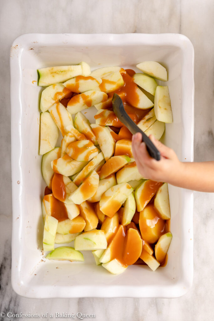 spatula mixing apples and caramel together in a ceramic dish on a marble surface