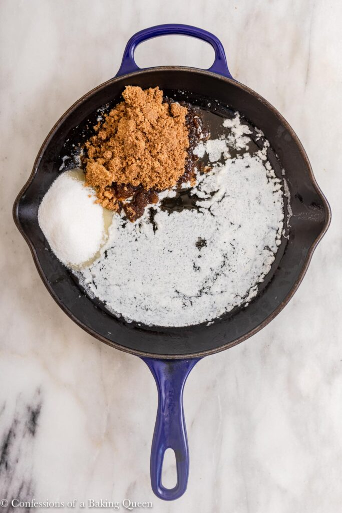 sugars and melted butter in a cast iron skillet on a marble surface