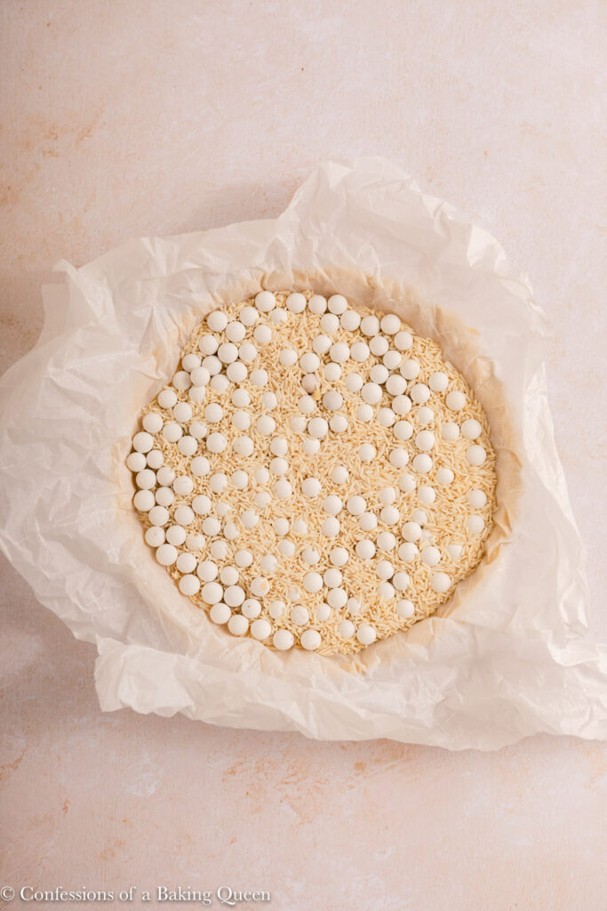 sweet shortcrust pastry covered wtih parchment paper filled with pie weights and dried rice before baking on a light surface
