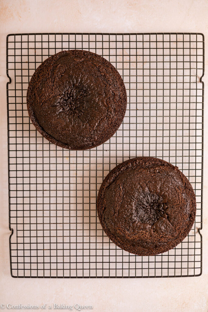 two chocolate cake layers cooling on a black wire rack on a light cream surface