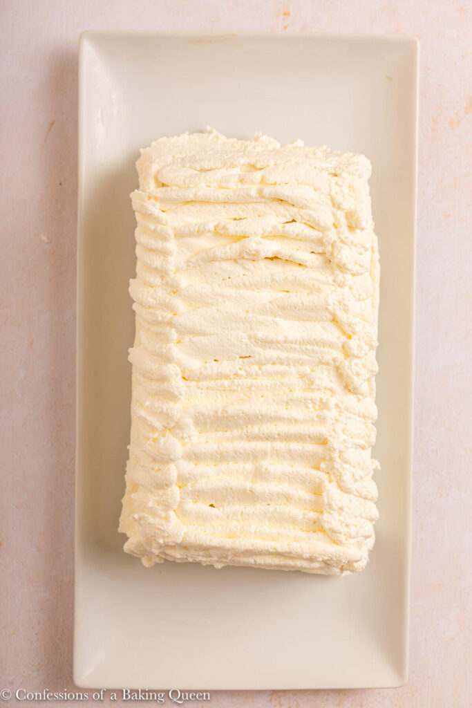 viennetta ice cream cake covered in whipped cream on a light cream surface
