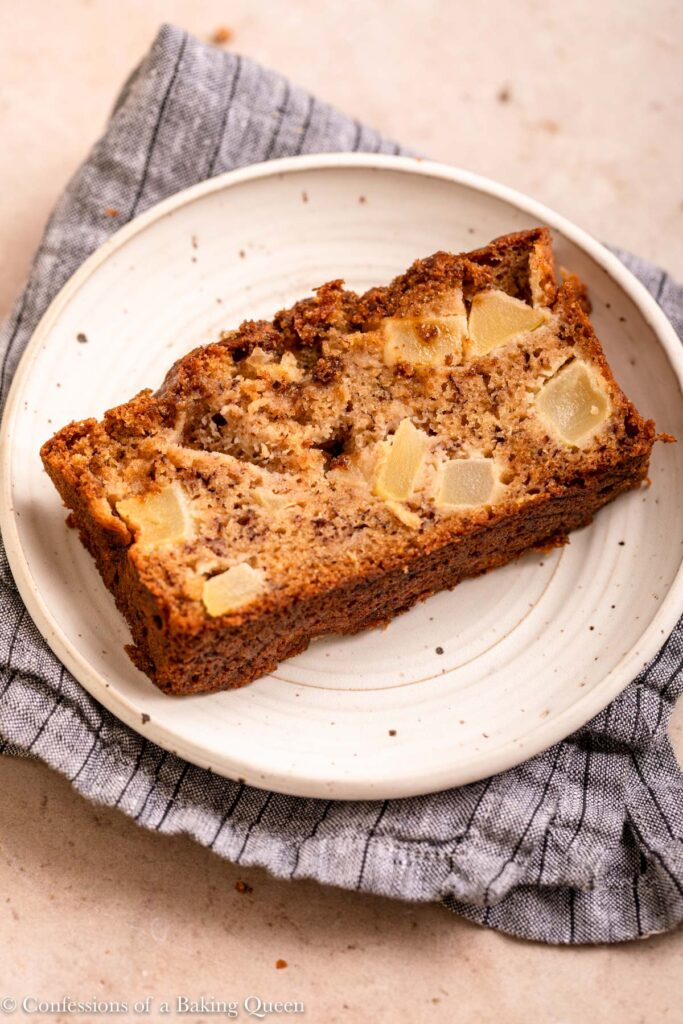 slice of apple banana bread on a white plate on top of a blue linen on a light brown surface