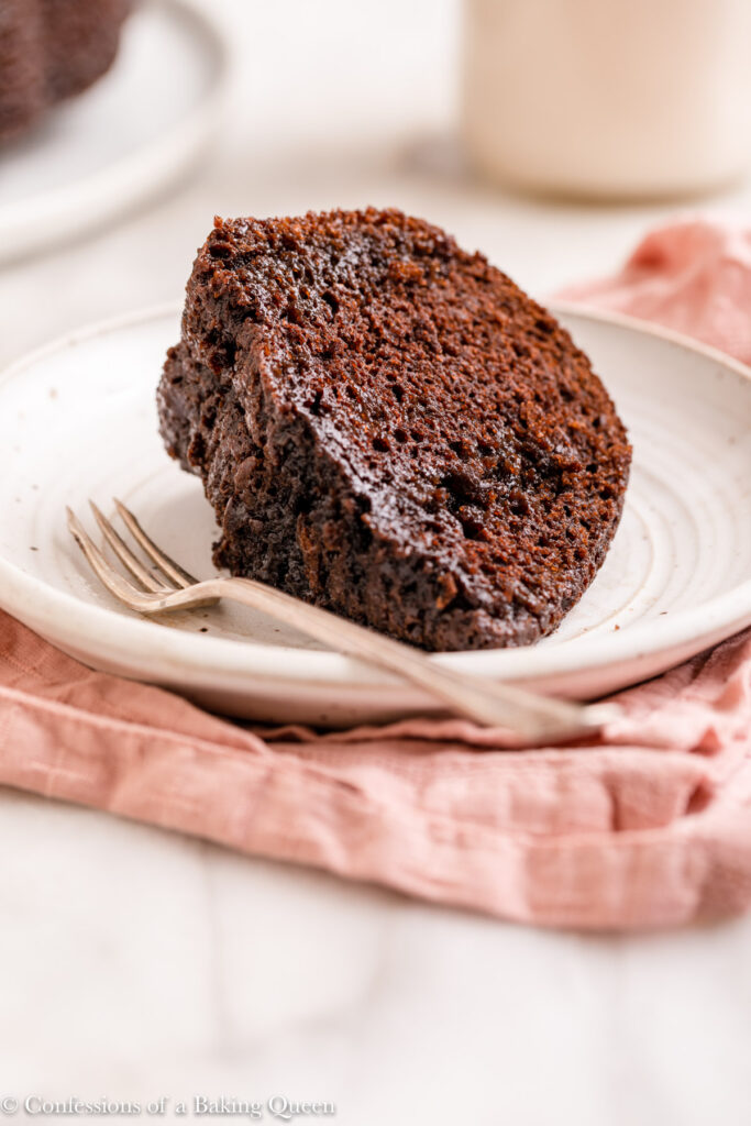 slice of red wine soaked chocolate bundt cake on a plate with a fork on a marble surface with a pink linen